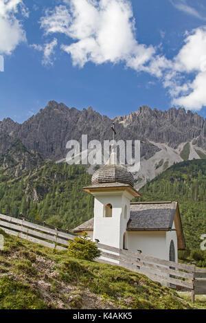 Chapel Before Erlspitz Group Belonging To Karwendelgebirge And Having Bizarre Weathering Forms Like Towers And Pinnacles - Stock Image