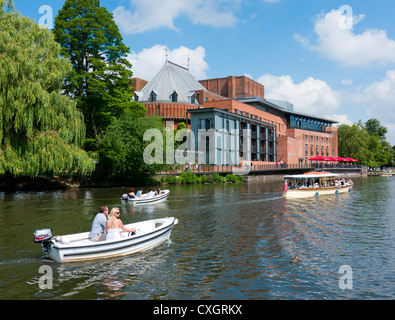 People in leisure boats on the river Avon next to the Royal Shakespeare Company Theatre, Stratford upon Avon, Warwickshire, - Stock Image