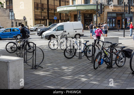 Bicycles parked and secured at the edge of the Southgate shopping area in the city of Bath with passersby and traffic in the background - Stock Image