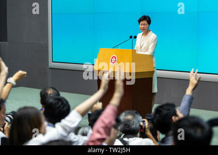 Members of the press trying to ask questions as the Hong Kong Chief Executive Carrie Lam speaks during a press conference at the government headquarters in Hong Kong. Carrie Lam apologised for the political unrest sparked by a proposed Beijing-backed law that would have allowed extraditions to mainland China. - Stock Image