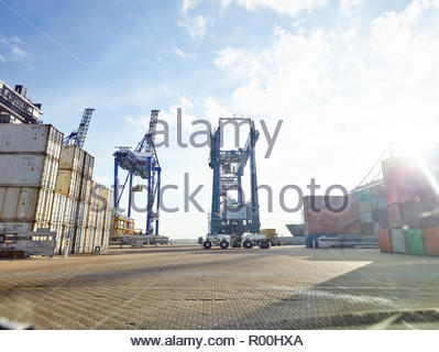 low angle view of cargo crane at port dockside with ship in background - Stock Image