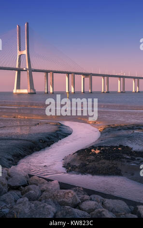 Vasco Da Gama Bridge at sunset, crossing the Tagus river, Parque Das Nacoes, Lisbon, Portugal - Stock Image