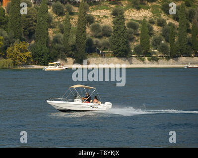 LAKE GARDA, ITALY - SEPTEMBER 2018: Two people on a small boat with outboard motor on Lake Garda. - Stock Image