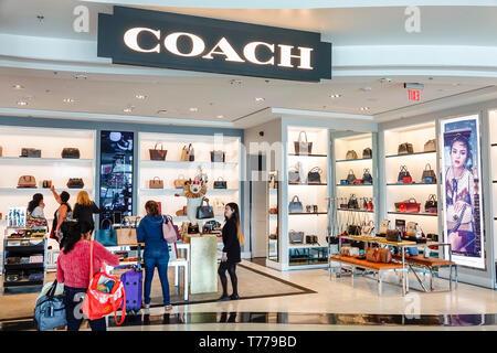 Miami Florida Miami International Airport MIA shopping Coach luxury brand handbags leather goods woman front entrance display sale - Stock Image