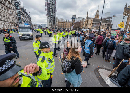 London, UK. 15th Mar 2019. Police finally remove students from the road outside Parliament - School students go on strike over the lack of action on climate change. They gather in Parliament square and march on Downing Street, blocking the streets around Westminster for over an hour. Credit: Guy Bell/Alamy Live News - Stock Image