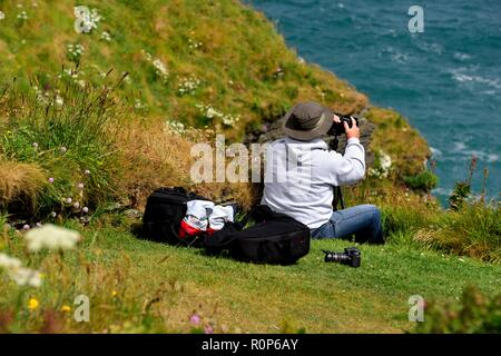 Photographer taking a photograph of the cornish coastline with camera and equiment bags behind him,Cornwall,England,UK - Stock Image