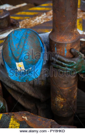 Worker holding rusty pipe on offshore oil platform - Stock Image
