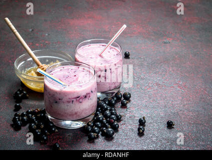 Black currant smoothie with honey and milk. On rustic background. - Stock Image