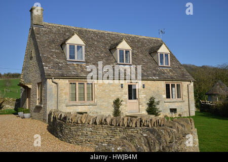 Riverside Cottage, Swinbrook which forms accomodation for The Swan Inn on the banks of the River Windrush near Burford, - Stock Image
