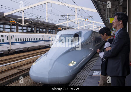 Two shinkansen (n700 series in front) in Himeji Station with people waiting for their train on the platform, Japan - Stock Image