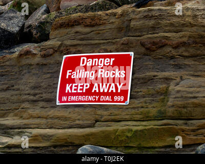Warning sign of the danger from falling rocks at the South end of Staithes beach North Yorkshire following a fatal accident to a girl there in 2018 - Stock Image