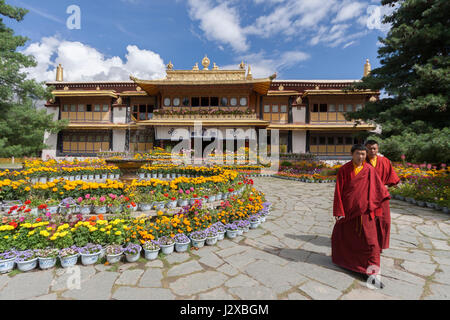 Two young Tibetan Buddhist monks walking in front of Norbulingka The Summer Palace in Lhasa, Tibet - Stock Image