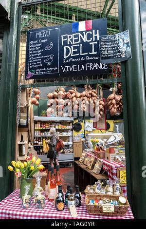 BOROUGH MARKET AUTHENTIC FRENCH DELI PRODUCE STALL  'Le Marché du Quartier' Authentic friendly charming French produce market stall display & menu blackboard with shopper browsing at Borough Market Southwark London UK - Stock Image