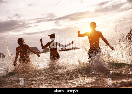 Group of happy friends run and jump at sunset sea beach. Tropical vacations concept - Stock Image