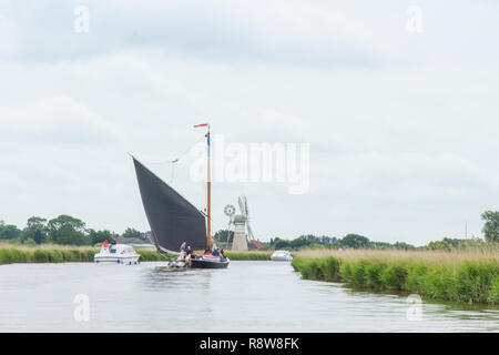 Wherry, traditional sailing boat on Norfolk Broads, River Thurne, in front of Thurne Dyke Drainage Mill. June. - Stock Image