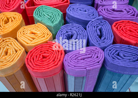 Loads of many rolled colorful light ratan carpets. Closeup - Stock Image