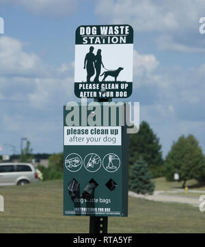 Dog waste station with supply of bags for cleanup in public park - Stock Image