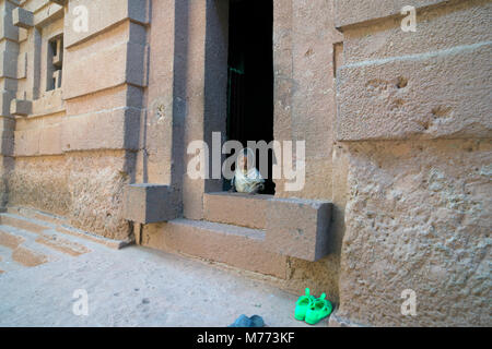 A young girl wearing a white robe looking through the doorway of a rock hewn church in Lalibela, Ethiopia. - Stock Image