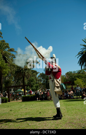 Adult man in period military costume, firing a muzzle-loading musket. - Stock Image