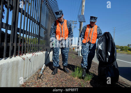 170412-N-IE405-134 SAN DIEGO (April 12, 2017) Master-at-Arms 2nd Class Jessica Fendzlau and Master-at-Arms 3rd Class Mayra Sanchez, both assigned to Naval Base San Diego, pick up trash during base cleanup. The all-hands event is hosted by Naval Base San Diego First Class Petty Officer Association in an effort to clean and improve the appearance of the naval base and promote morale. (U.S. Navy photo by Mass Communication Specialist 2nd Class Indra Bosko/Released) - Stock Image