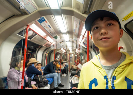 A young boy travels on a London Underground train while ona day trip to London. - Stock Image