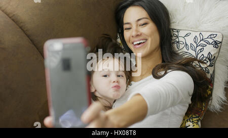 High angle selective focus view of playful mother and daughter posing and taking selfie with smartphone on sofa - Stock Image