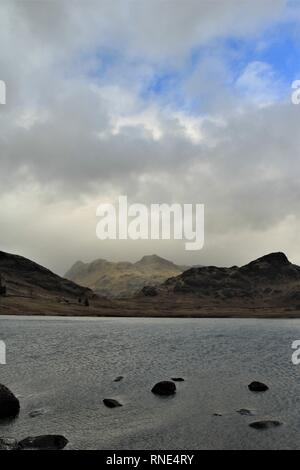 Cumbria, UK. 18th Feb, 2019.  18th February 2019. UK Weather. Sunshine and Showers from Blea Tarn in the English Lake District Cumbria UK. Credit C.Hall / Alamy Live News Credit: greenburn/Alamy Live News - Stock Image
