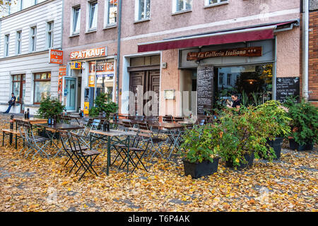 La Galleria Italiana restaurant and Spatkauf convenience store In Torstrasse with carpet of Autumn leaves, Mitte Berlin. - Stock Image