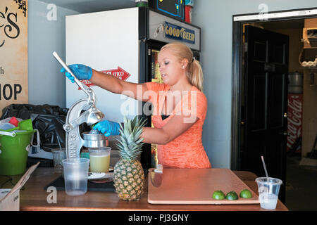 Young blond woman or girl preparing or squeezing fresh fruit including lime and pineapple for a small local restaurant and bar in Destin Florida, USA. - Stock Image