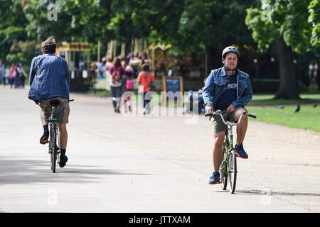 London, UK. 10th August, 2017. Cyclists ride through Kensington Gardens this morning as the sunshine makes an apparition in London, UK. Credit: BSFUK/Alamy Live News. - Stock Image