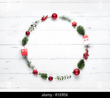 Christmas wreath made of fir branches, apple and berry on white background. Flat lay - Stock Image