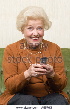 Senior woman using cell phone - Stock Image
