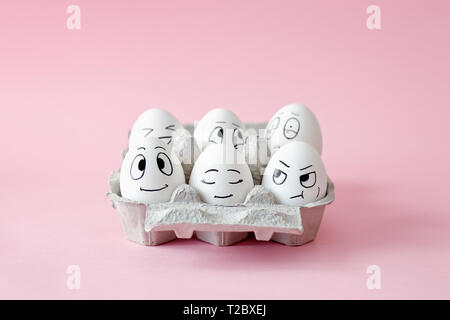 Funny Easter eggs with facial expressions. Eggs with different faces in egg carton. - Stock Image