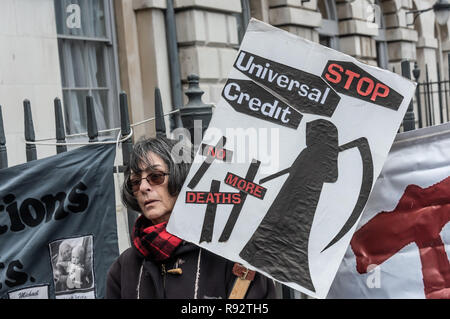 London, UK. 19th Dec, 2018. Maggie Zolobuaijluk holds a placard with the grim reaper and message 'Stop Universal Credit - No More Deaths' at the protest by DPAC in support of the parliamentary debate due later in the day on the cumulative impact of the cuts on the lives of disabled people. They say the government cuts and changes in benefits, along with inappropriate benefit sanctions, have had a disproportionate effect on disabled people, resulting in great hardship, denying people their rights and many deaths. Credit: Peter Marshall/Alamy Live News - Stock Image