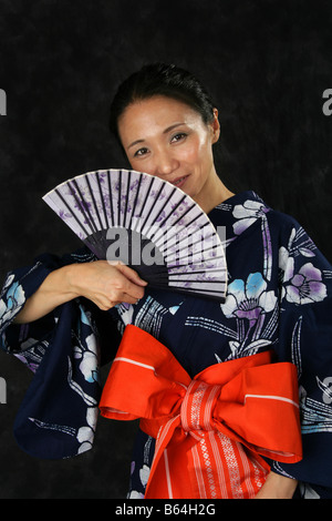 Japanese Woman in a Blue Kimono with a Fan. - Stock Image