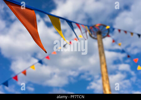 Colorful flags on the background of blue sky and clouds, Latvia - Stock Image