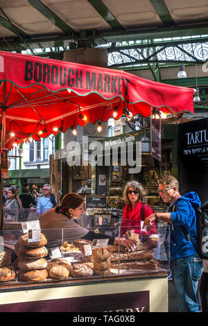 Borough Market Bakery and customers. Speciality bread Borough Market Bakery 'Bread Ahead' stall inside interior with variety of attractive hand made artisan breads on display for sale. Artisan speciality bakery stall at Borough Market Southwark London UK - Stock Image