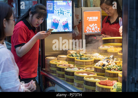 People waiting at a street food shop in Shanghai, China - Stock Image