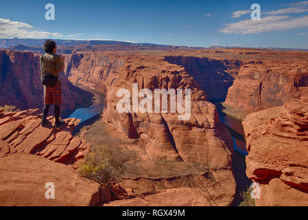 man hiker looking over Horseshoe Bend of Colorado River in Page, Arizona - Stock Image