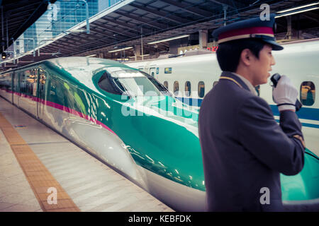 On Japan Railways both the trains and the service are polished. A shinkansen leaves Tokyo Station with a guard in - Stock Image