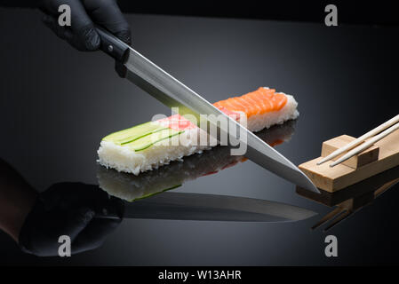 chef prepares sushi, cuts with a knife. sushi on black background with reflection - Stock Image