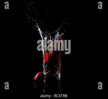 Tall glass strawberry splash with strawberry fruit on dark background - Stock Image
