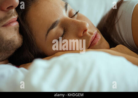 Young woman resting in bed with partner - Stock Image