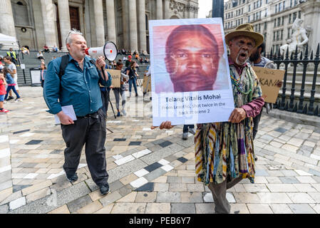London, UK. 13th August 2018. Three days before the 6th anniversary of the massacre when 34 striking miners were shot dead by South African police at Lonmin's Marikana platinum mine, protesters march from St Paul's Cathedral for a tour of the City of London visited investors, insurers and shareholders profiting from the violence against people and nature in Marikana and heard about the colonial roots of the huge wealth of the City. Credit: Peter Marshall/Alamy Live News - Stock Image