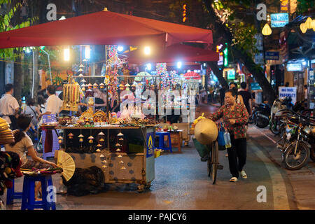 Night shot of one of the many busy streets that comprise Hanoi's Night Market in the Old Quarter, Vietnam. The popular market takes place on weekend e - Stock Image