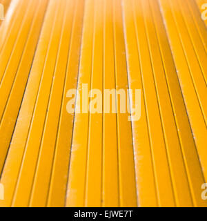 Cross view of yellow metal with shallow depth of field - Stock Image