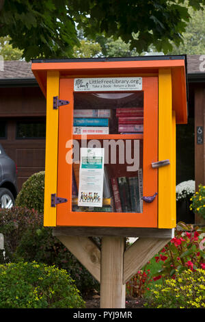 'Little Free Library' box with books for sharing in a Canadian residential neighbourhood. - Stock Image