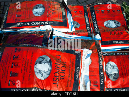 A stack of bags of peat free wool and bracken compost for sale in a garden centre - Stock Image