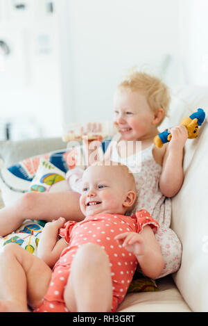 Happy children on sofa - Stock Image
