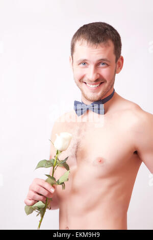 Cheerful muscular young man posing with a rose - Stock Image